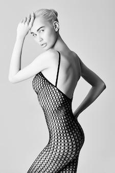 바닥에 앉아 섹시 란제리 누드 여자 금발. 메쉬에 검은 에로틱 속옷 누드 완벽한 알몸 여자. 흰색 배경에 포즈 누드 소녀