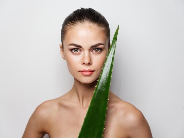 裸の女性のきれいな肌の美容と緑のアロエの葉