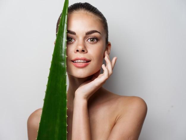 裸の女性のきれいな肌の美容と緑の葉の顔