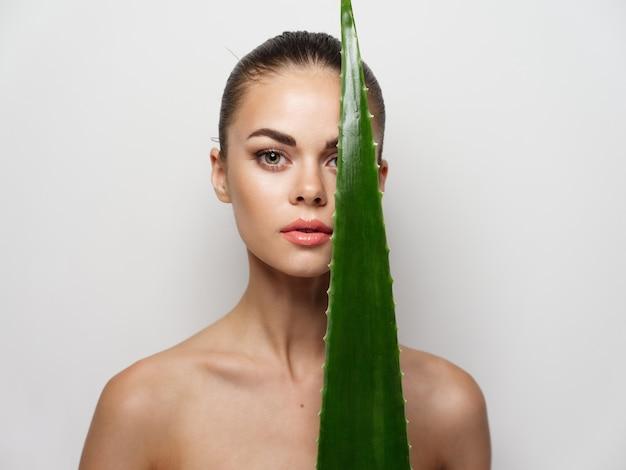 裸の女性のきれいな肌の美容メイクと緑のアロエの葉