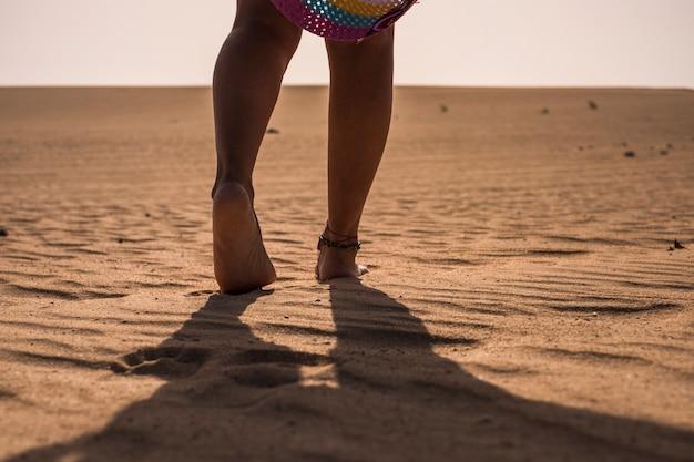 砂漠のビーチの砂の上を柔らかく歩く裸の女性の足-夏休み休暇の人々の概念-地平線の白い空と一人の女性が一人で歩く