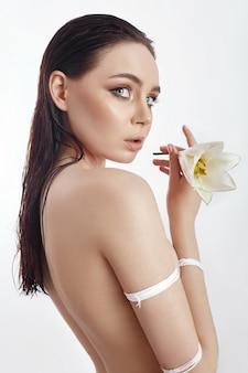 흰색 분홍색 백합 꽃으로 밧줄로 묶인 누드 여자. 젖은 머리, 얼굴 피부 관리를 가진 소녀입니다. 텍스트, copyspace에 대 한 장소입니다. 완벽한 피부, 보습, 주름 개선을 위한 누드 브루넷