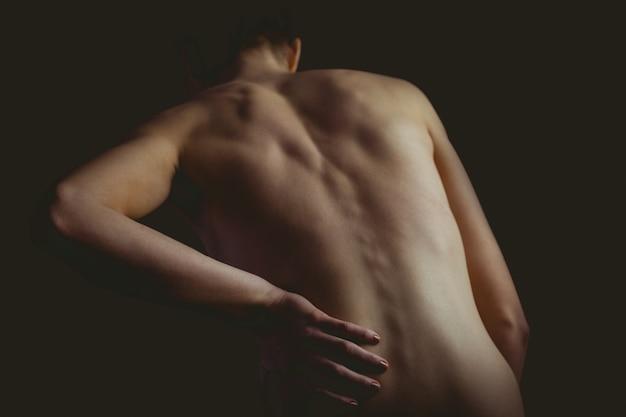 Обнаженная женщина с травмой спины