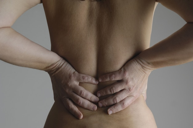 Nude woman with a back pain