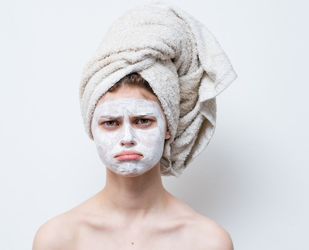 Обнаженная женщина с белым кремом на лице и полотенцем на голове