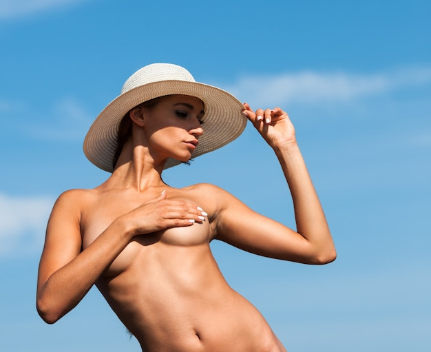 Nude woman with a white hat on the beach