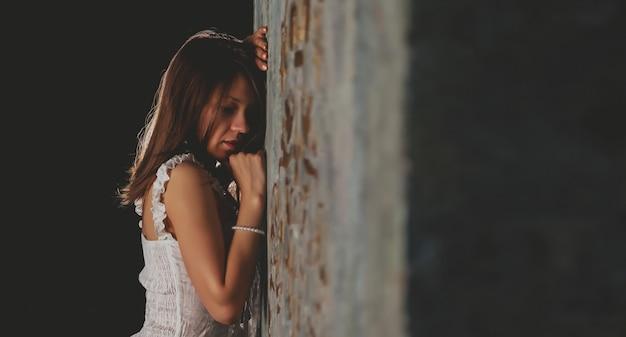 질감된 빈티지 벽에 누드 젊은 섹시 한 여자. 속옷 없이 흰색 프렌치 코르셋을 입은 귀여운 소녀. 벌거벗은 날씬한 여자 배우가 감정을 보여줍니다. 알몸의 일부가 포함된 성인 성인 누드 콘텐츠
