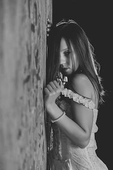 Обнаженная молодая сексуальная женщина против текстурированной старинной стены. симпатичная девушка в белом французском корсете без нижнего белья. обнаженная стройная актриса демонстрирует эмоции на фотосессии. контент для взрослых с обнаженной частью тела