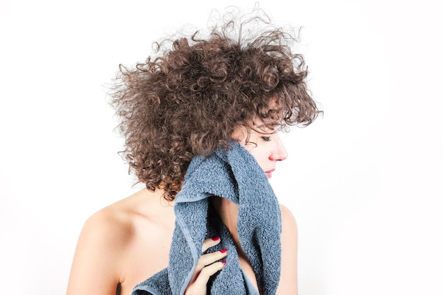 Nude young woman with curly hair wipes her face with towel against white backdrop