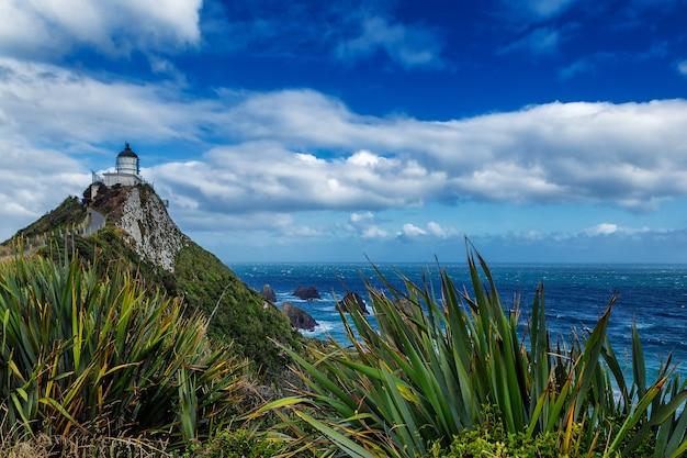 Наггет пойнт маяк и красивый природный ландшафт с облаками в небе