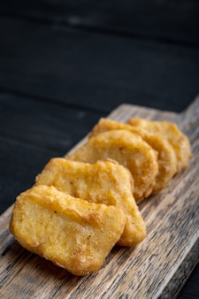 Nuggets breaded on black wooden table,.