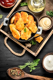 Nuggets from chicken meat with sauces on a tray. on the black chalkboard.