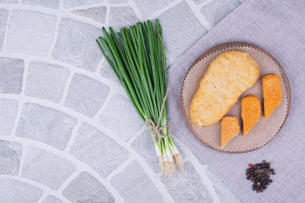 Pepite su una tavola di legno con un mazzo di cipolle verdi