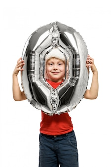 Number 0 of a silver balloon in the hands of a blond boy in a red santa hat