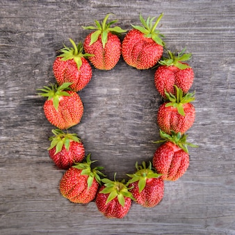 Number 0 of strawberries on wooden background
