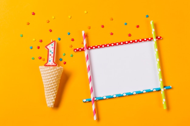 Number 1 candle with colorful star sprinkles over the waffle cone and blank frame on an orange backdrop
