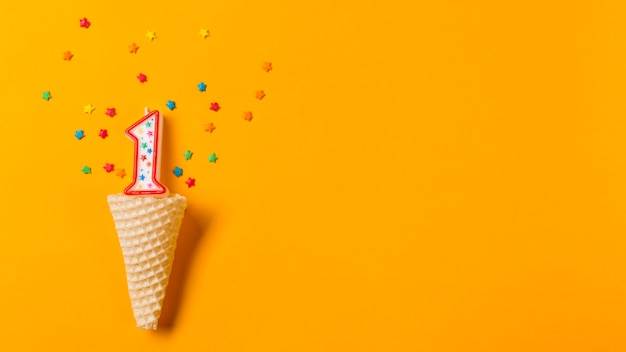 Number 1 candle with colorful star sprinkles over the waffle cone on an orange backdrop