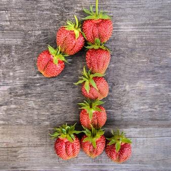 Number 1 of strawberries on wooden background