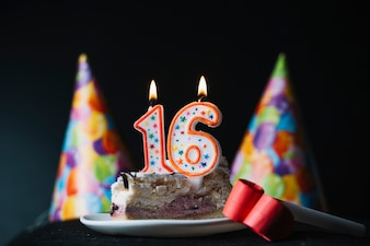 Number 16 birthday lighted candle on the slice of cake with party hat and party horn blower