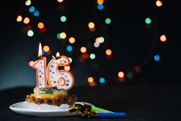 Number 16 birthday lighted candle on the slice of tart with party horn blower against illuminated bokeh backdrop