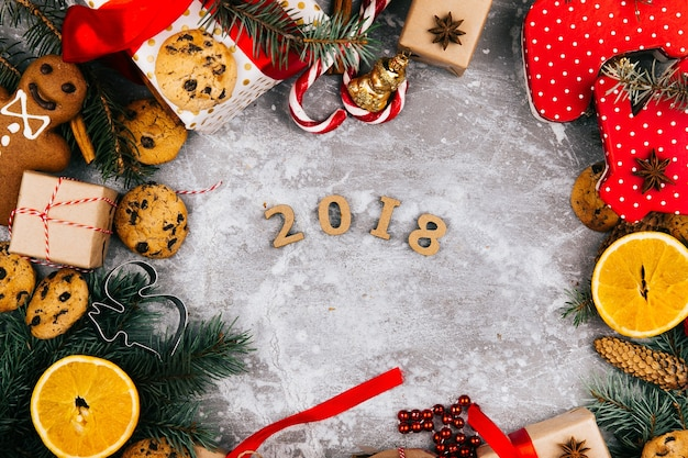 Number 2018 lies in the center of a circle made of oranges, cookies, fir branches, red present boxes and other kinds of christmas decor