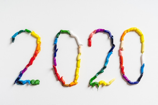 The number 2020 are painted on white canvas with bright oil paints. top view close up.