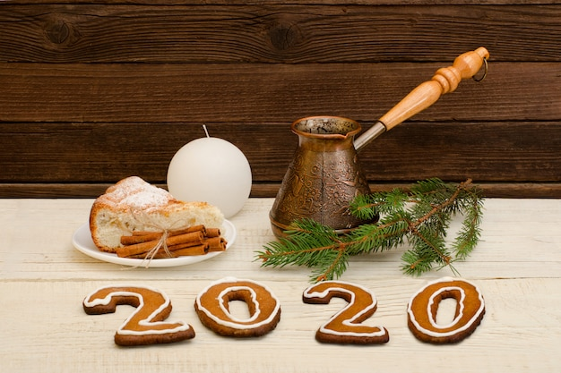 Number 2020 from gingerbread cookies. cezve, pie, spruce branches and candle. christmas