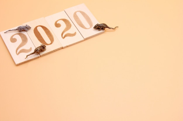 Number 2020 lined with wooden figures and three little metal mice on it.