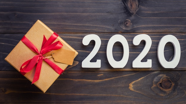 Number 2020 for new year and brown gift box on a wooden table