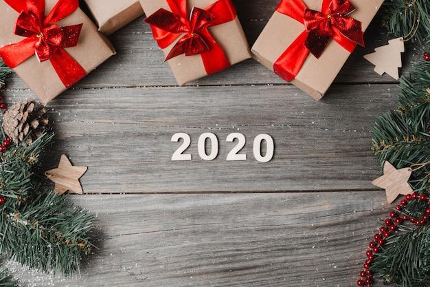 Номер 2020 с рождественскими подарками и украшениями на деревянном фоне.