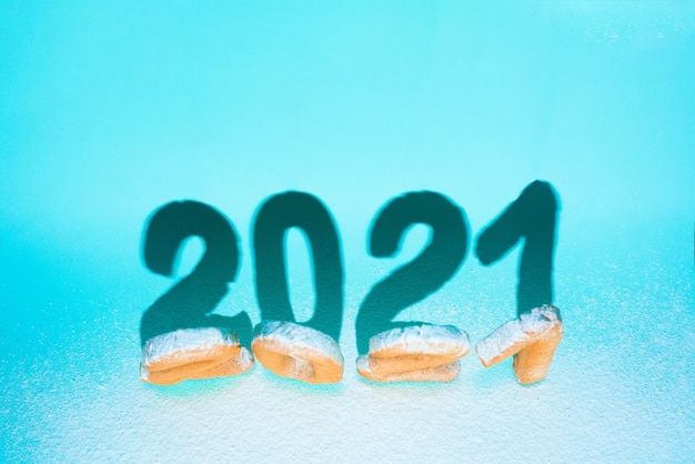 Number 2021 of ginger cookies sprinkled with powdered sugar, hard shadows on a blue wall . festive new year wall, template for greeting cards. conceptual design, space for text.