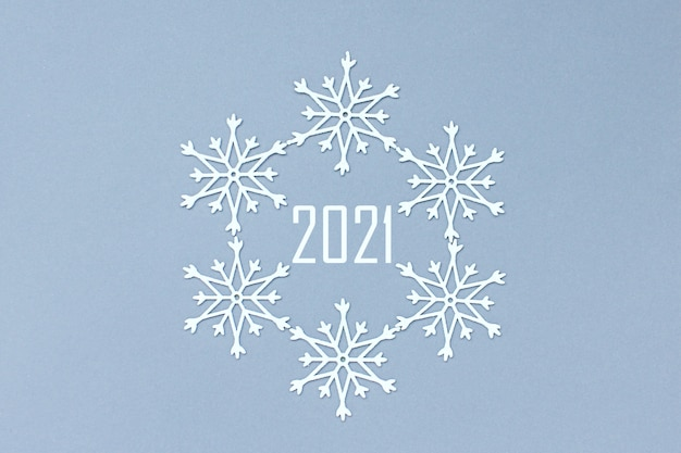 番号2021は雪片の円の中にあります。灰色の背景に白い装飾的な雪。