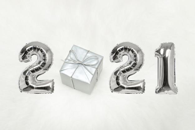 Номер 2021 из серебряных воздушных шаров. подарочная коробка. белый фон. концепция нового года.