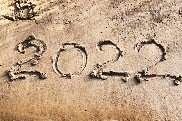 Number 2022, drawn on wet sand on coast. merry christmas and happy new year concept