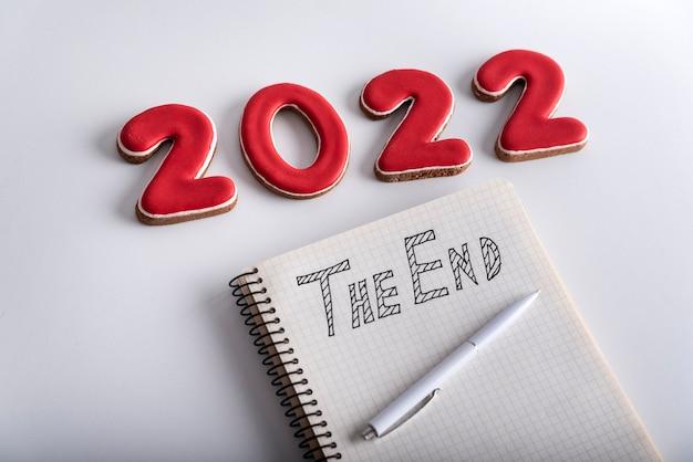 番号2022、theendの碑文が付いたペンとノートがクローズアップ。白色の背景。