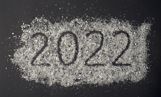 暗い背景に散らばったキラキラに書かれた番号2022フラットレイトップビュー