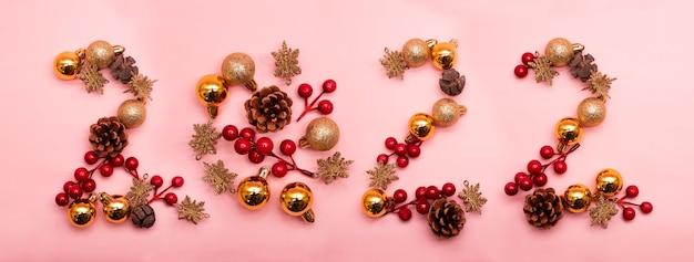 분홍색 배경에 크리스마스 장식품으로 작성된 번호 2022