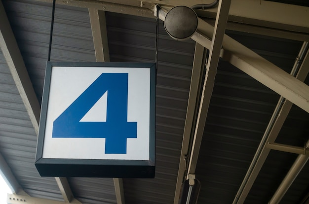 Number 4 display on hanging billboard or light box at airport or subway train platform station