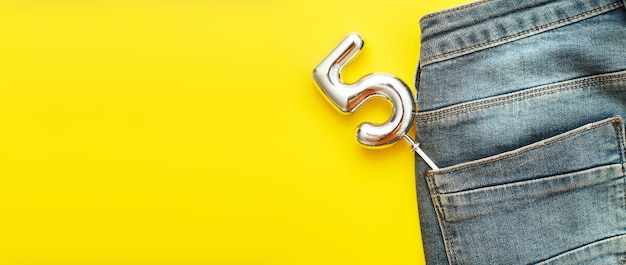 Number 5 sticking out of the back pocket of blue jeans on a yellow background