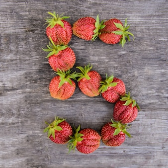 Number 5 of strawberries on wooden background