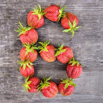 Number 6 of strawberries on wooden background