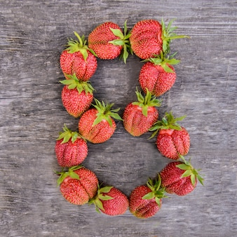 Number 8 of strawberries on wooden background