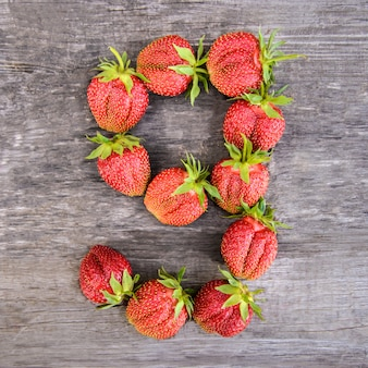 Number 9 of strawberries on wooden background