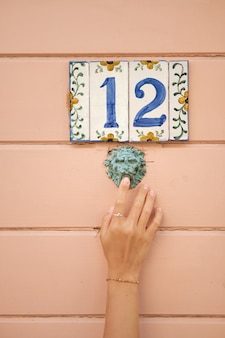 Number beautiful house number on painted ceramic tiles girl presses the doorbell retro style