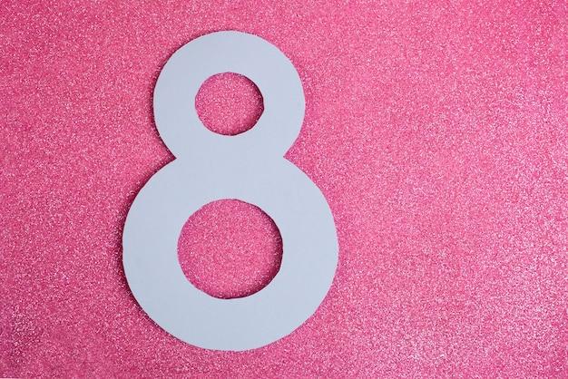 Номер восемь вырезан в бумаге на фоне розового блеска. хорошо для 8 марта, международный женский день вертикальный баннер.