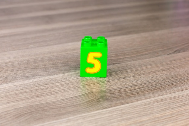 Number five on alphabet blocks displayed on an orange background. learning to count with numbers