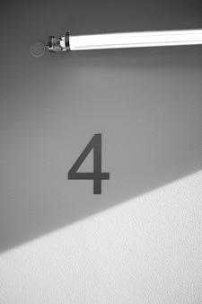 Numero quattro sulla parete sotto la luce al neon