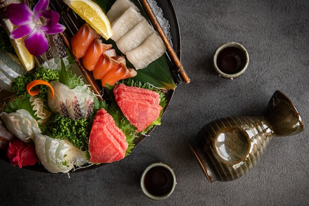 A number of fresh sashimi are placed on a plate chopsticks and soy sauce are placed