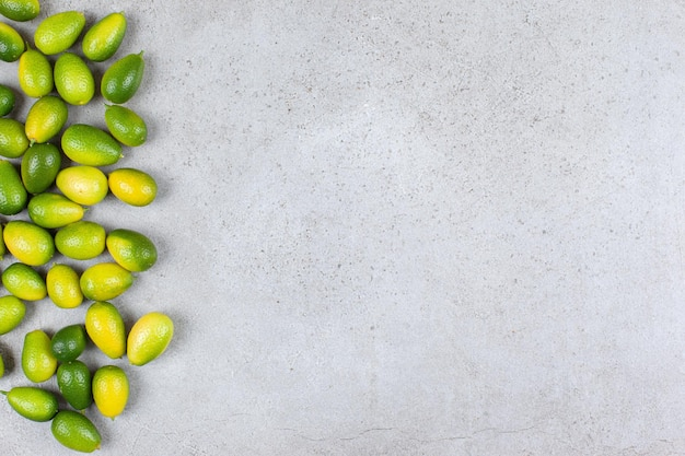 A number of kumquats scattered on marble background.