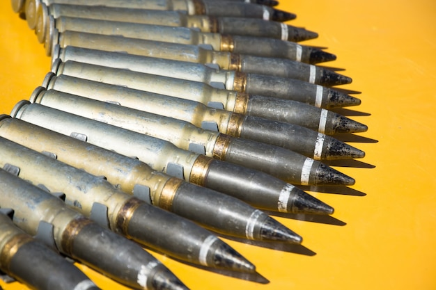 黄色の背景に半円で折りたたまれた機関銃のカートリッジの数。